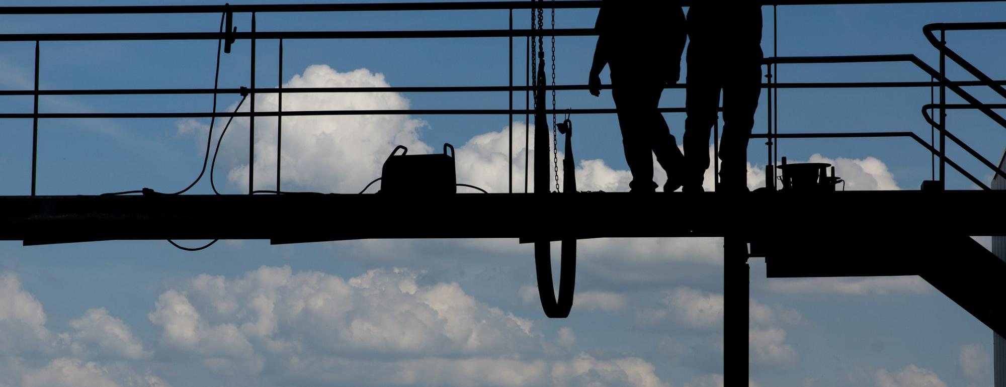 men in hardhats on scaffolding with blue sky in background