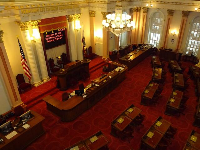 California State Senate assembly room with red carpet and wood desks